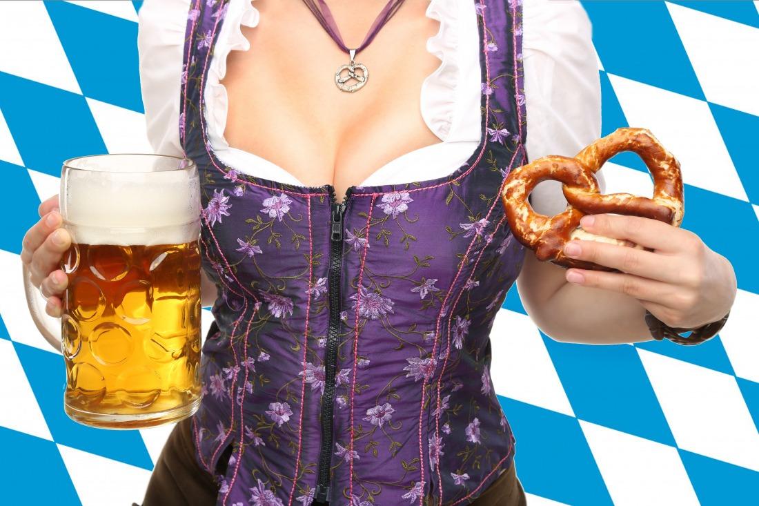 Oktoberfest: Frau im Dirndl mit Maß und Brezn